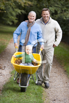 Royalty Free Photo of a Grandfather and Father Pushing a Baby in a Wheelbarrow