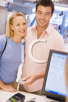 Royalty Free Photo of a Woman Smiling at a Man Paying a Clerk With a Credit Card