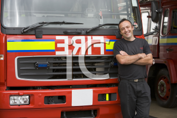 Royalty Free Photo of a Firefighter in Front of a Truck