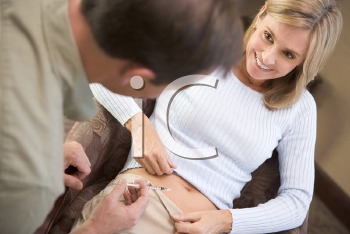 Royalty Free Photo of a Man Putting a Needle in a Woman's Stomach
