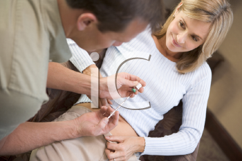Royalty Free Photo of a Man Helping a Woman Put a Needle in Her Stomach