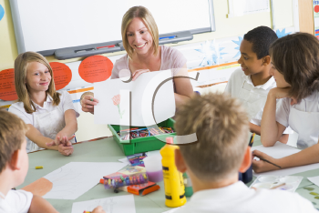 Royalty Free Photo of a Teacher Showing a Drawing to a Class