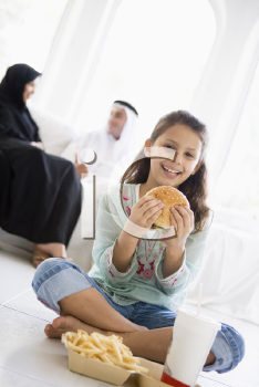 Royalty Free Photo of a Child Eating Fast Food With Her Parents Behind Her