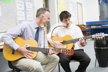 Royalty Free Photo of a Teache and Guitar Student