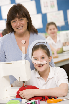 Royalty Free Photo of a Girl Sewing and a Teacher Behind Her