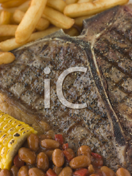 Royalty Free Photo of a T-Bone Steak with Fries, Corn and Beans