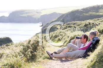 Royalty Free Photo of a Couple on a Cliff With Binoculars