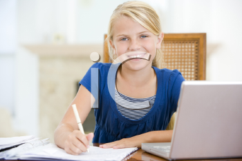 Royalty Free Photo of a Smiling Girl Doing Homework