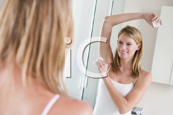 Royalty Free Photo of a Woman Putting on Deodorant