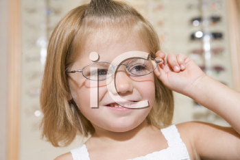 Royalty Free Photo of a Girl Trying on Glasses