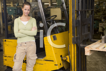 Royalty Free Photo of a Female Warehouse Worker Beside a Forklift
