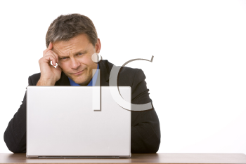 Royalty Free Photo of a Frowning Businessman at a Laptop