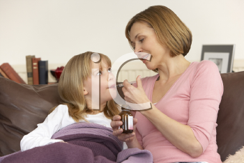 Royalty Free Photo of a Mother Giving Her Daughter Medicine