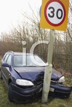 Royalty Free Photo of a Car Against a Speed Limit Sign