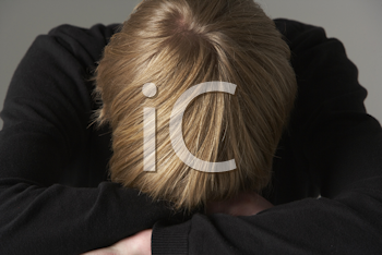 Royalty Free Photo of a Boy With His Head Bowed