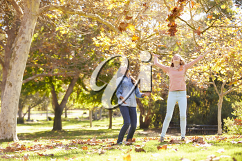 Two Girls Throwing Autumn Leaves In The Air