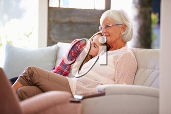 Grandmother With Adult Granddaughter Watching TV On Sofa