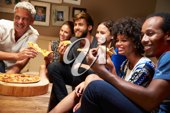Friends eating pizza at a house party, watching television