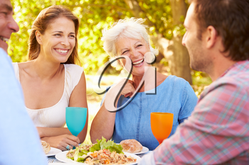 A senior and a young adult couple eating together outdoors
