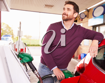 Young man refuelling a car at a petrol station