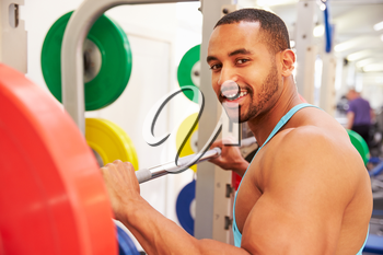 Smiling man holding barbells on a rack at a gym