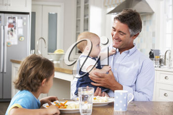Father, Son And Baby Daughter Having Meal In Kitchen Together