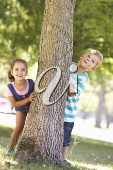 Two Children Hiding Behind Tree In Park