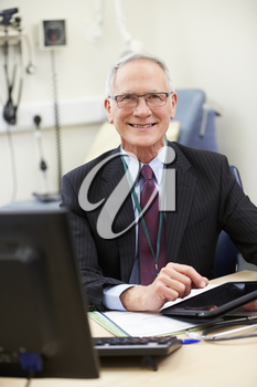 Male Consultant Working At Desk Using Digital Tablet