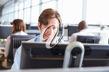 Male call centre worker, looking at screen, close-up