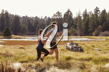 Man and woman running in nature near a lake, close up