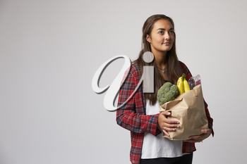 Studio Portrait Of Female Nutritionist With Bag Of Food