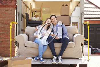 Family With Sofa On Tail Lift Of Removal Truck Moving Home