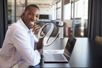 Young black man in office with laptop smiling to camera