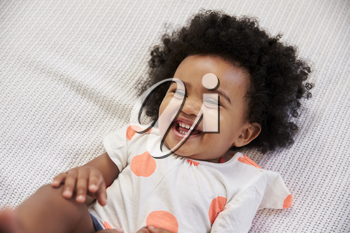 Parent Tickling Laughing Baby Girl Lying On Bed
