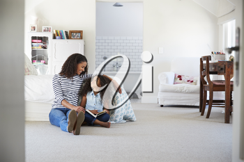 Mother and daughter reading a book in girl's room