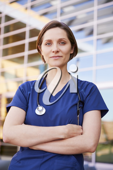 Smiling white female healthcare worker outdoors, vertical