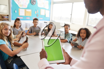 Teacher and kids using tablets in elementary school lesson