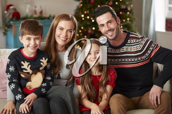 Portrait Of Parents With Children Wearing Festive Jumpers Sitting On Sofa In Lounge At Home On Christmas Day