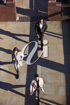 Aerial view of three business people walking in the same direction on a sunny urban street, vertical