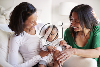 Millennial mixed race mother sitting in an armchair holding her three month old baby son, her mother kneeling beside them
