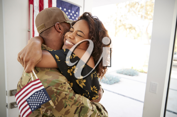 Millennial black soldier embracing his wife after arriving back home,close up