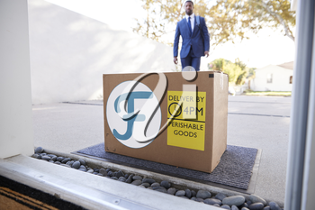 Businessman Coming Home To Fresh Food Home Delivery In Cardboard Box Outside Front Door