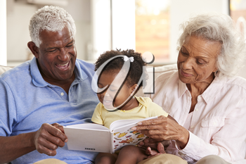 Grandparents Sitting On Sofa At Home Reading Book With Baby Granddaughter