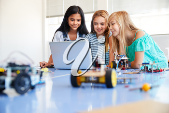 Three Female Students Building And Programing Robot Vehicle In After School Computer Coding Class