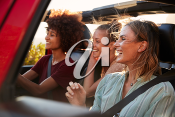 Three millennial female friends on a road trip driving together in an open jeep, close up