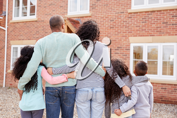 Rear View Of Family Standing Outside New Home On Moving Day Looking At House