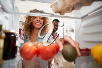 View Looking Out From Inside Of Refrigerator As Couple Open Door And Unpack Shopping Bag Of Food
