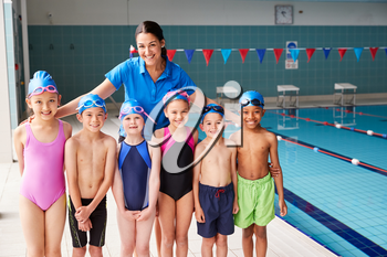 Portrait Of Female Coach With Children In Swimming Class Standing Edge Of Indoor Pool