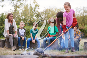 Female Team Leader With Group Of Children On Outdoor Activity Trip Cooking Meal Over Camp Fire
