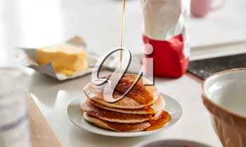 Maple Syrup Being Poured On Stack Of Freshly Made Pancakes Or Crepes On Table For Pancake Day
